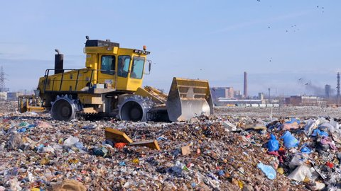 A landfill truck levels out the first garbage layer at a junkyard.