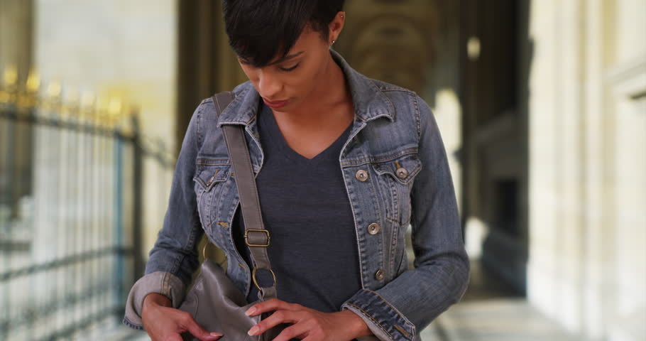 Young black woman looks through her purse for something important in outdoor hallway. Attractive African-American woman digging through her handbag. 4k | Shutterstock HD Video #35016805