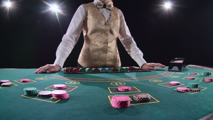 Casino stickman in gold vest takes the cards from card holder at the game table. Black background. Bright light. Slow motion