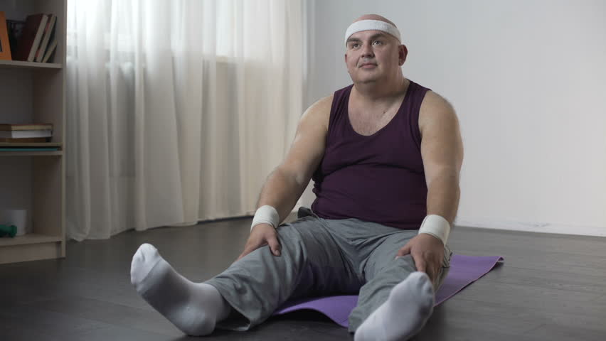 View of funny overweight man doing yoga at home, trying to sit in lotus pose