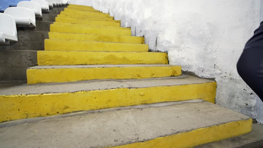 Running Stairs - man runner sprinting up staircase in HIIT run exercise. Fit male athlete exercising sprint up stairway