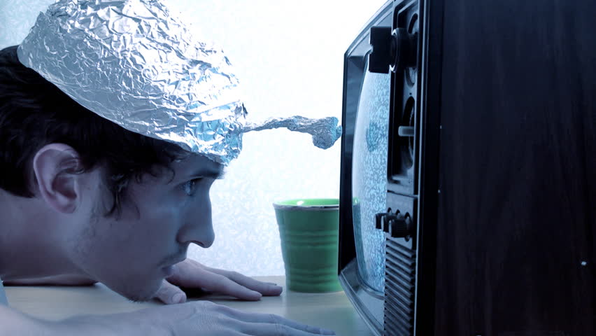 Crazy young man with a tinfoil hat watching a TV tuned with fuzzy reception, probably seeing aliens.