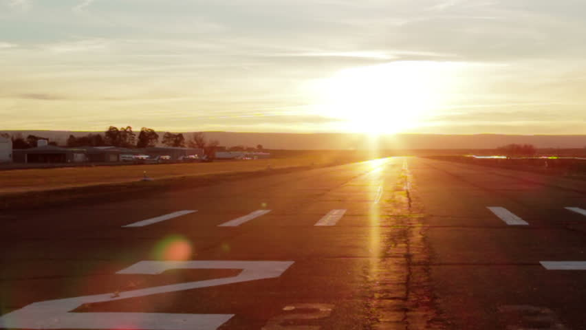 A small airplane flies over and lands in a brilliant sunset.