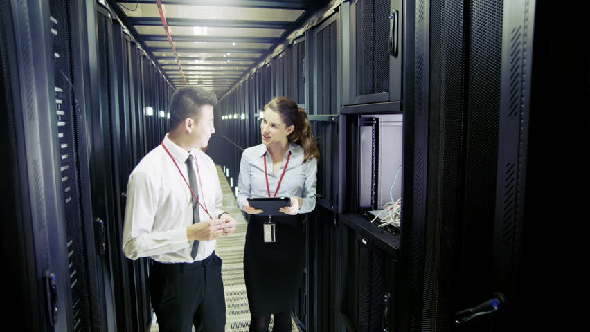 Three people of mixed ethnicity are working in a data center with rows of server racks and super computers. They are walking up and down and checking all of the equipment.  | Shutterstock HD Video #3510905