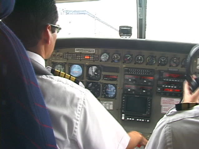 2 pilots inside cockpit prepare for takeoff