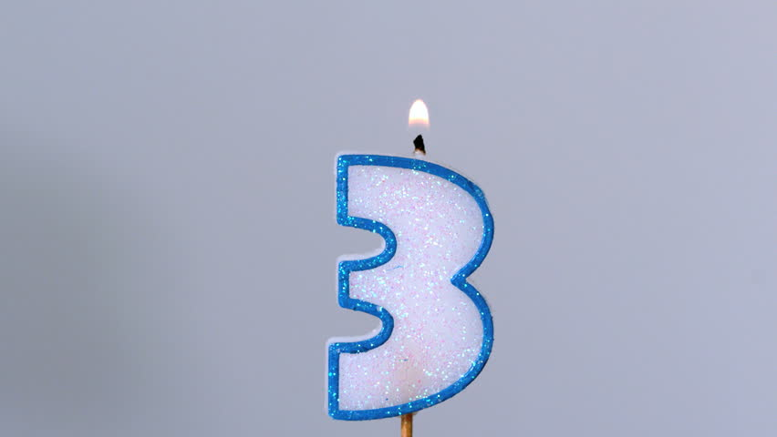 Three birthday candle flickering and extinguishing on blue background in slow motion