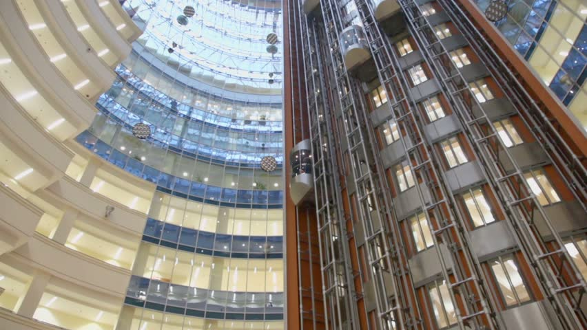 Elevators ride at multilevel building with transparent roof, view from below in motion