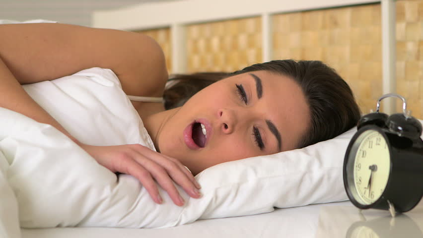 Woman yawning and waking up in bed