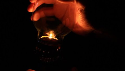 Man preparing an old fashioned lantern in darkness. How to light an oil lamp. Place the lamp on a hard, level surface. Carefully lift the glass chimney up. Raise the wick up by turning the thumbwheel.
