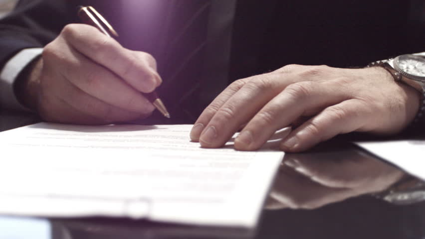 Businessman sitting at shiny office desk signing a contract with noble pen | Shutterstock Video #3582926