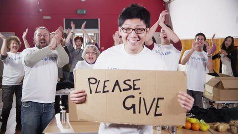 "A male charity volunteer of Asian ethnicity holds up a ""Please Give"" sign and smiles at the camera as his fellow volunteers applaud and cheer in the background. In slow motion."