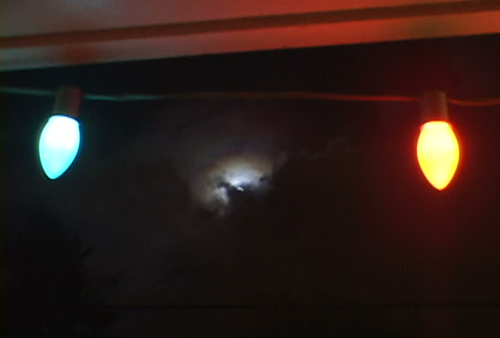 Full Moon with great storm layering clouds over night skyline with Christmas light string in foreground.