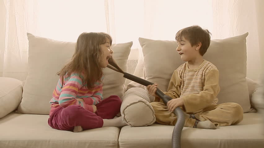 Adorable laughing kids playing at home with vacuum cleaner.