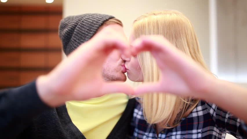 Couple kissing make heart-shape with hands