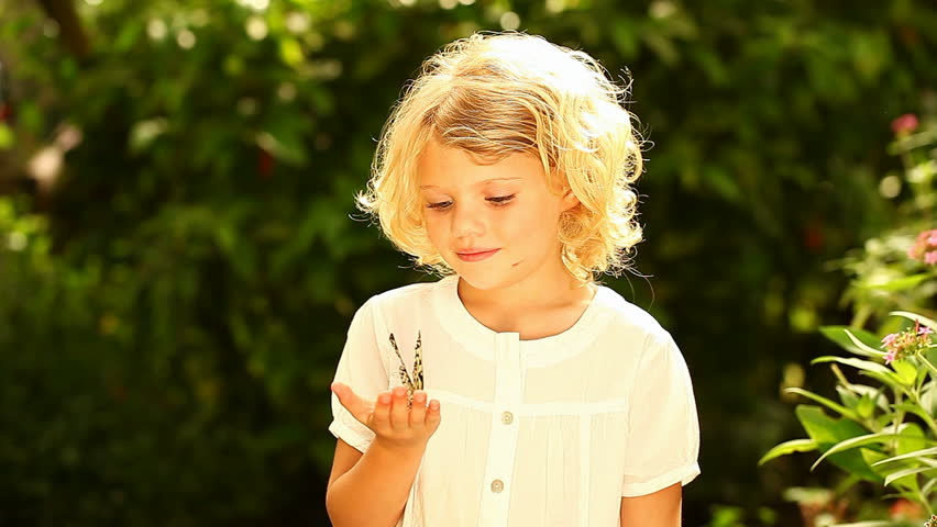 Young girl in nature holding a rice paper butterfly until it takes off, circles her and makes her smile.