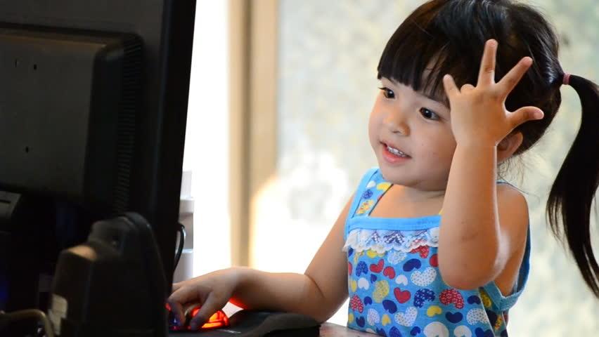 cute asian little girl play computer (three action shot)