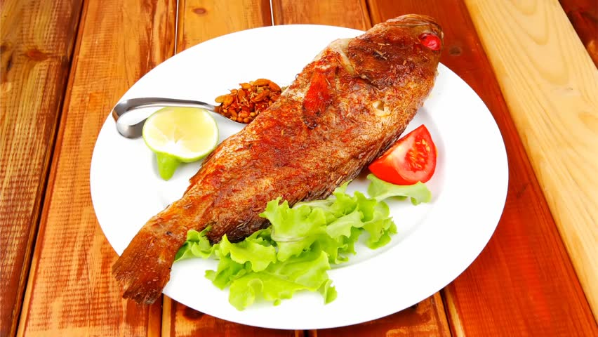 Main course roasted sea fish on plate with tomatoes for Fish on main