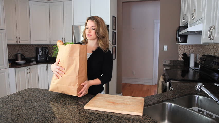 Woman In Her Kitchen With Groceries Bought From The Market In A Brown Paper Bag