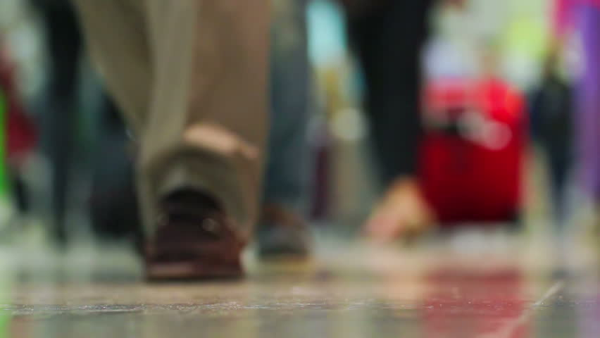 Crowd of people walking with luggage in the international airport, de-focused scene | Shutterstock HD Video #3619385