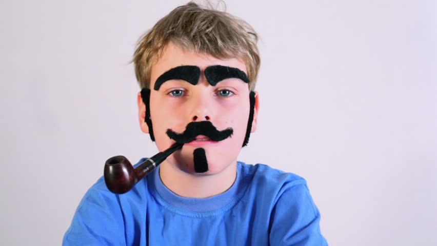 Little boy in blue shirt with pipe, fake mustache, eyebrows, beard and sideburns looks at camera