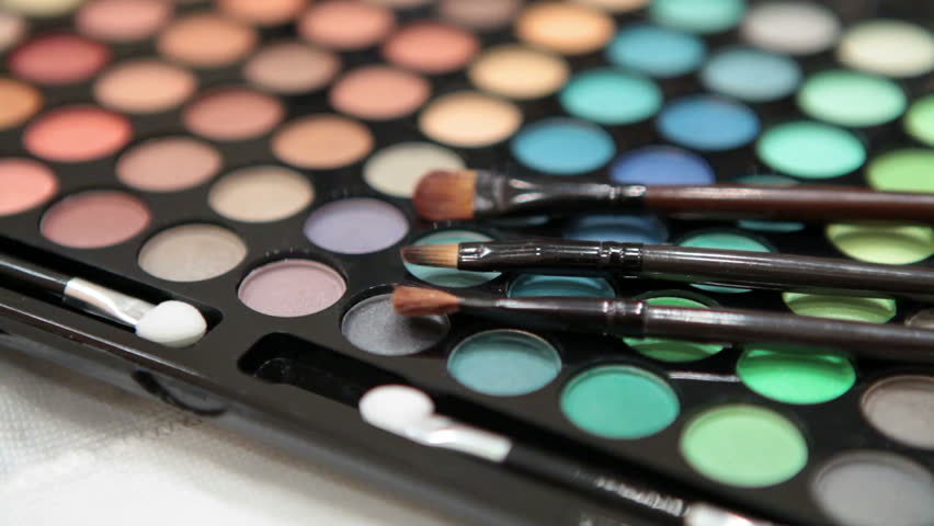 Make-up brushes laying on colorful cosmetic palette. Camera rotation