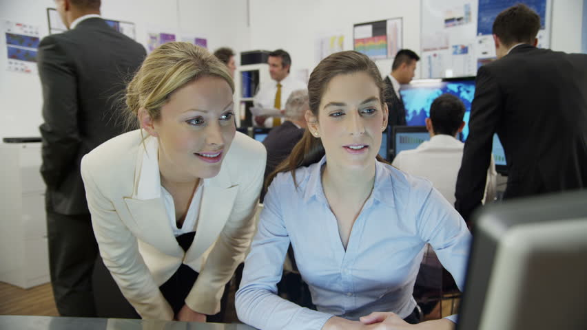 Two attractive female financial traders are working in a busy office filled with computers. They are discussing share prices, as the rest of their team can be seen hard at work in the background. | Shutterstock HD Video #3672125
