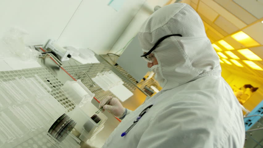 "Scientist / technician preps silicon wafers to go into a kiln during silicon chip manufacture in a clean room. They are wearing full body white ""bunny suit"" coveralls to avoid contamination."