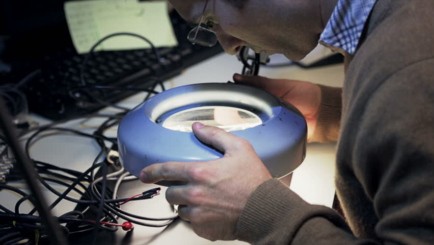 Young engineer repairing an electronic circuit board with a magnifying glass