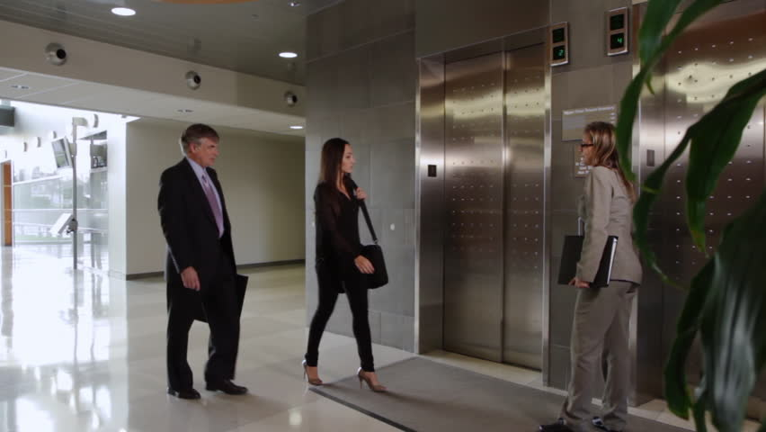 Business people call an elevator, get in when it arrives. Wide view, recorded