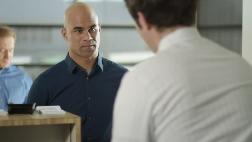 Male customers conduct business at a bank. Over the shoulder shot from behind