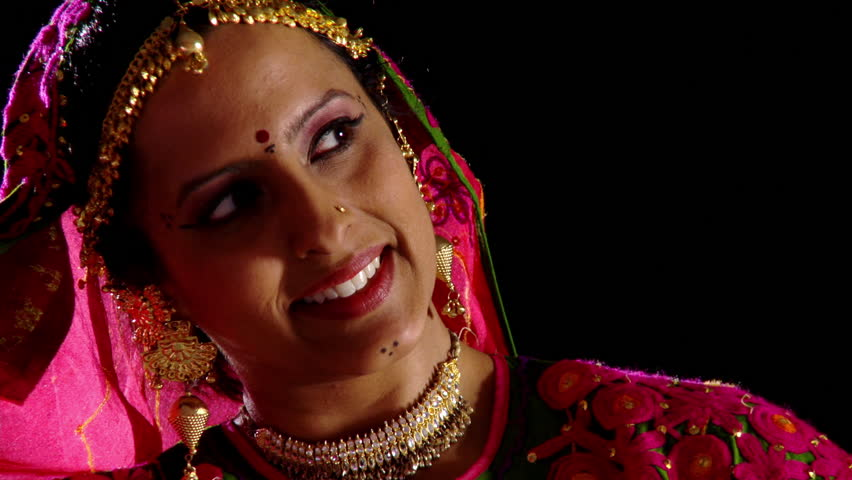 Indian girl in traditional dance costume reveals her face briefly and  smiles at something off-screen, then covers her face again.