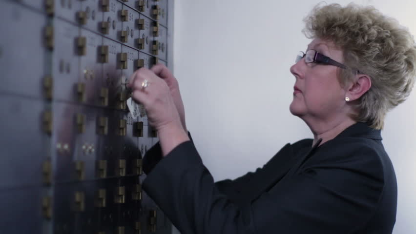 Woman opens up a safe deposit box and removes contents. Medium close up inside