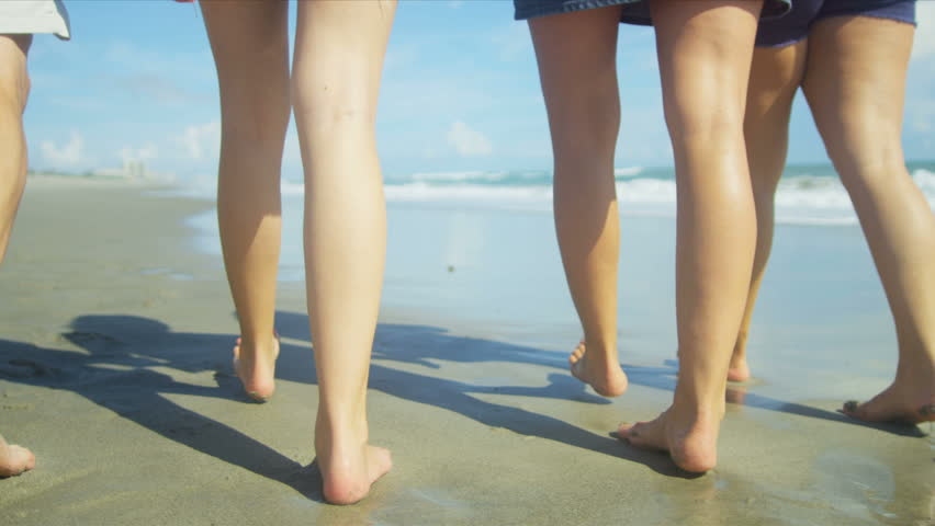 Legs of Caucasian family walking barefoot on beach shot on RED EPIC