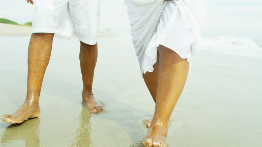 legs of mature african american couple walking barefoot on beach