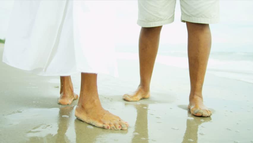 lower body legs feet senior ethnic male female walking in ocean