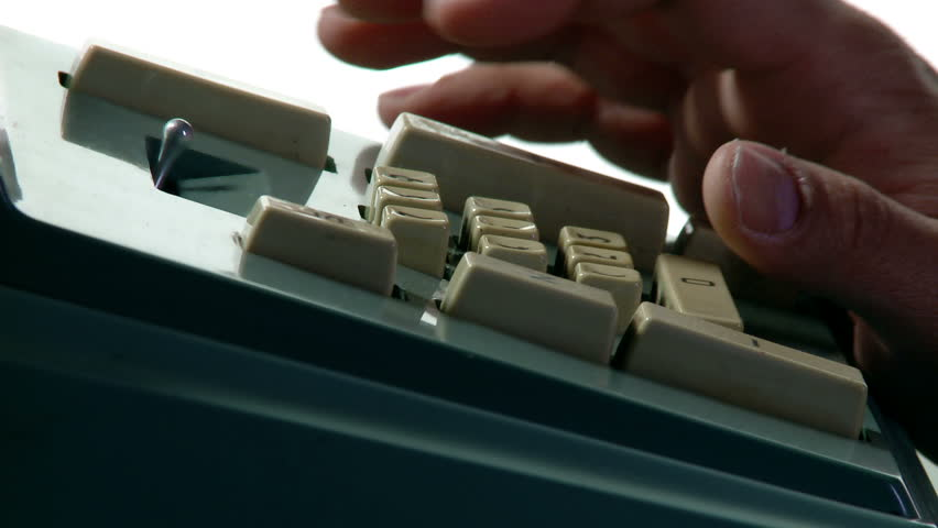 Tight close up on fingers operating an old-fashioned adding machine.