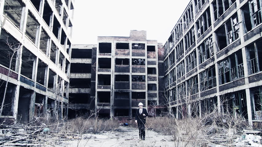 Developer walks into shot and looks around at the ruined buildings around him, making notes. Wide shot with cold blue tones, high-contrast and dramatic filtration.