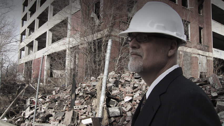 Developer walks into shot and looks around at the collapsed buildings around