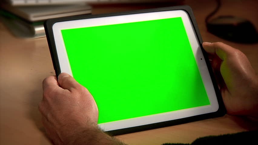 A man uses a tablet PC at his desk.  Chroma key screen for placement of your own content.