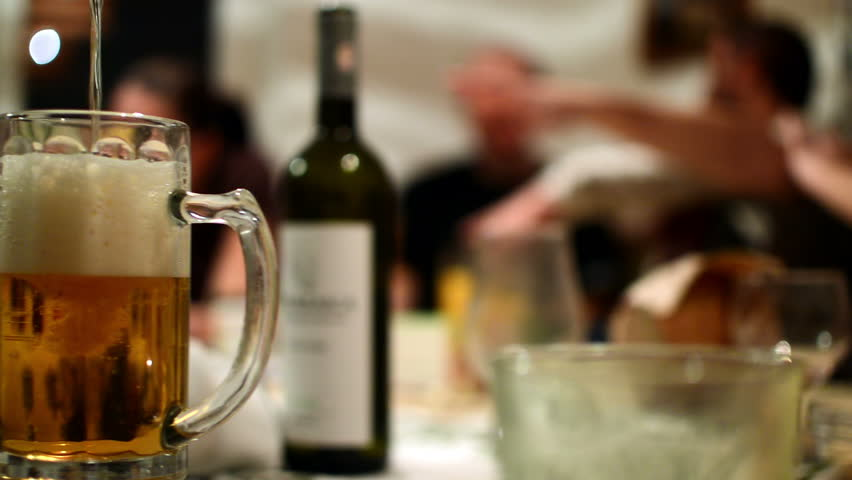 pouring beer in mug at party