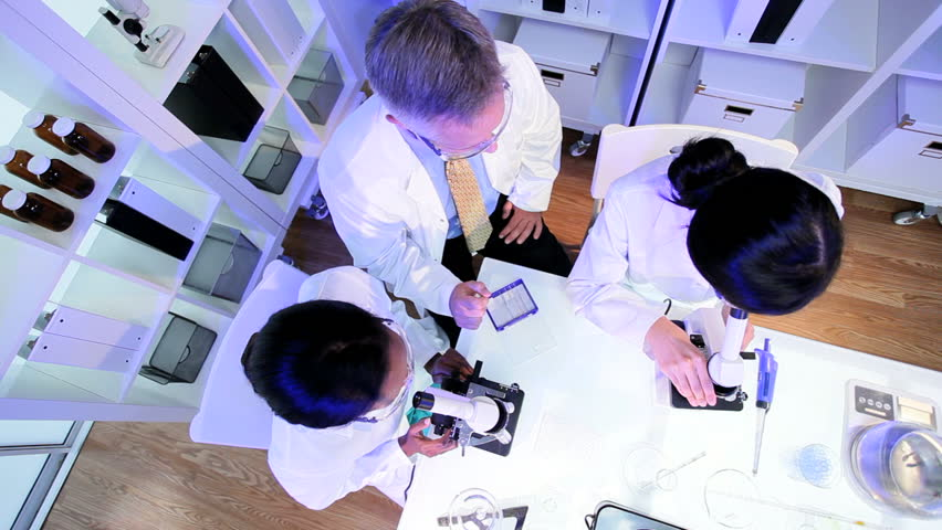 Overhead view three student doctors working with microscopes in hospital laboratory | Shutterstock HD Video #3772385
