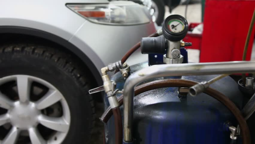 Gas cylinder with pressure gauge stands near car with open hood in automobile service station