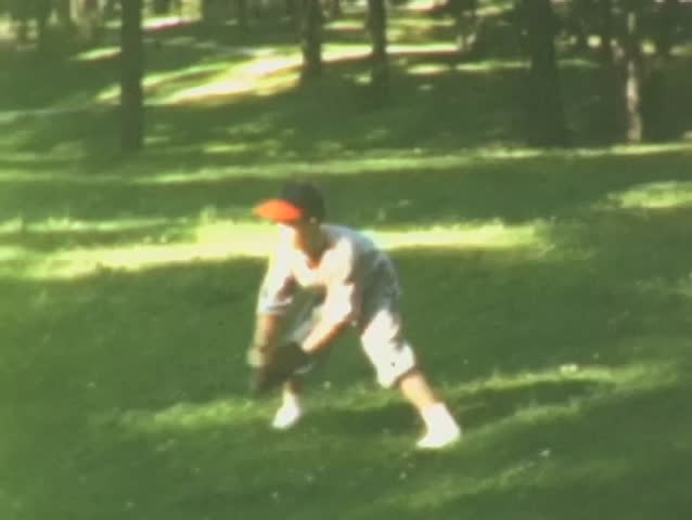 Young baseball player in green grass plays catch in summertime in St. Louis, Mo.
