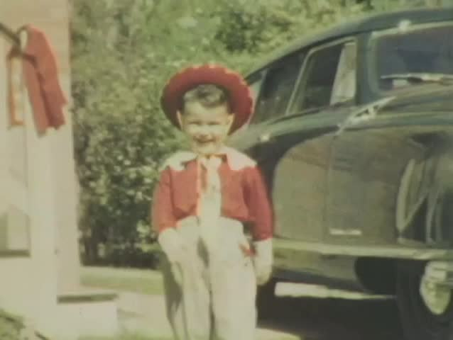 Smiling 3 year old boy in red cowboy outfit walks down stairs and by antique car, then smiles while walking into the camera