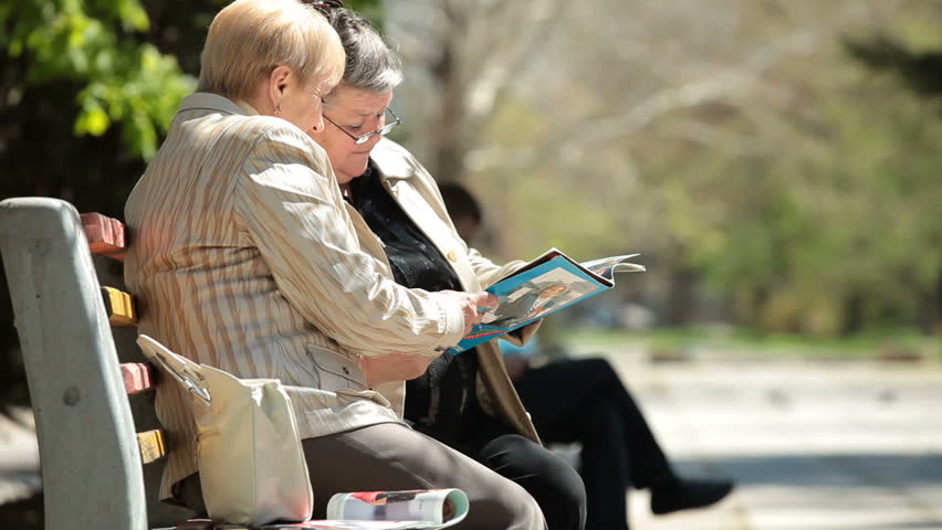 Senior women friends reading glossy magazines in the city park