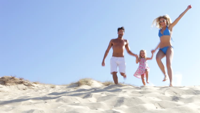 Family in swimwear running down sand dune towards camera position. Shot on Canon 5d Mk2 with a frame rate of 30fps
