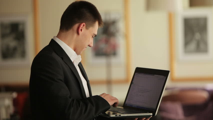 Young man with notebook typing something and smiling
