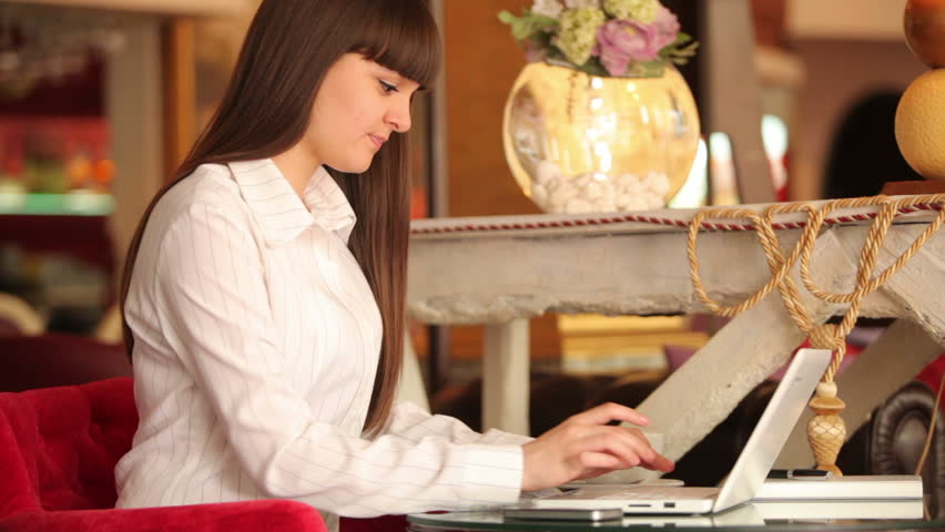 Businesswoman  typing on a laptop and sitting at cafe