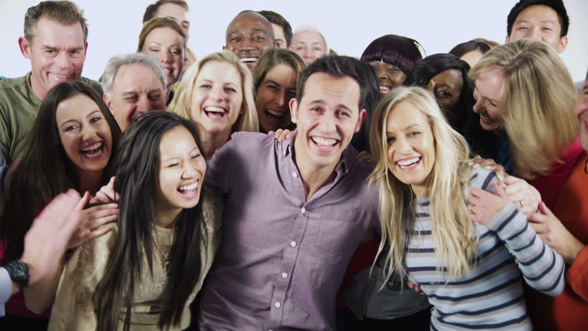 Portrait of a large and diverse multi ethnic group of people who are standing together, in brightly colored casual clothing and having fun. They are isolated on white in a studio shot.