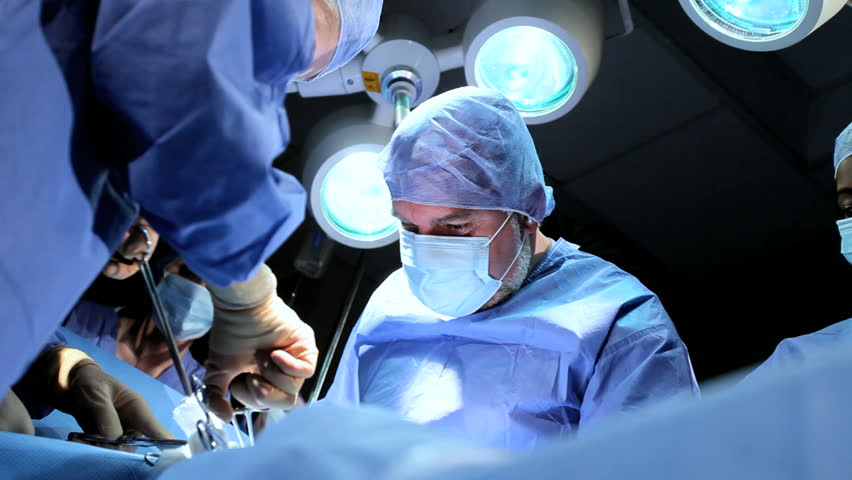 Doctor wearing protective clothing performing surgery using sterilised equipment | Shutterstock HD Video #3813875